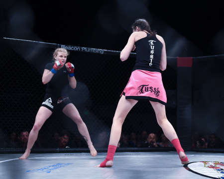 Female MMA fighters facing each other.