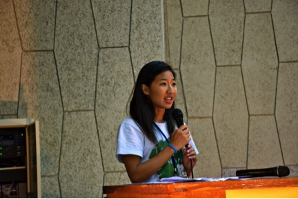 The author, Sunny Yang, holding a microphone and being the MC for the closing ceremony of the summer pre-service training.