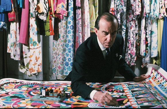 Reed College grad Pucci at his work table surrounded by hanging garments.